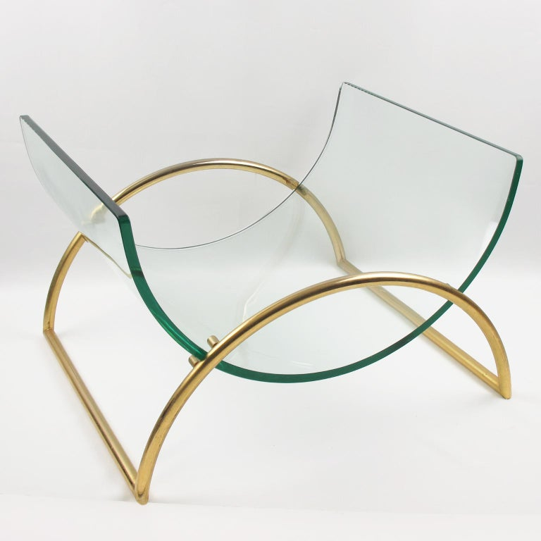 Elegant 1970s modernist magazine rack holder stand by Italian designer Gallotti & Radice. Featuring lyre shape design with curved thick clear glass shelf held within a curved gilded aluminum holder in an exact reverse curved position. Made of best
