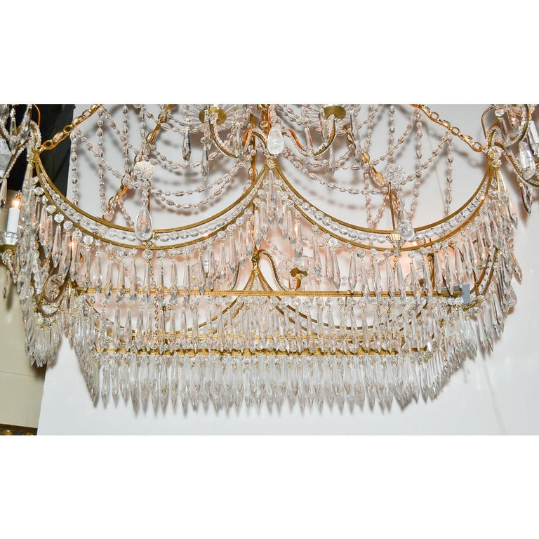 A most unique Italian gilt brass and crystal elongated chandelier. The crown adorned with icicle and pear-shaped prisms atop an abundance of cascading bead cut crystals, and scrolling arms with flower-petal bobeche. The base lavishly draped with a