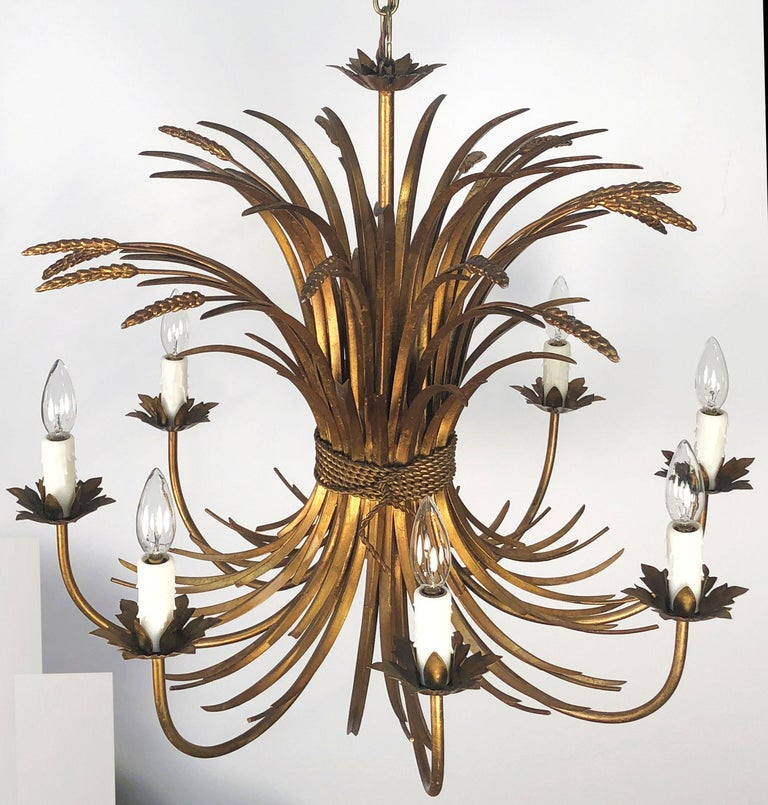 A handsome Italian eight-light hanging light fixture or chandelier or pendant light of gilt metal featuring a wheat sheaf (wheatsheaf) design, with floral bobeches and lovely foliate scroll accents.  Measures: 28 1/2 inches diameter  U.S. wired,