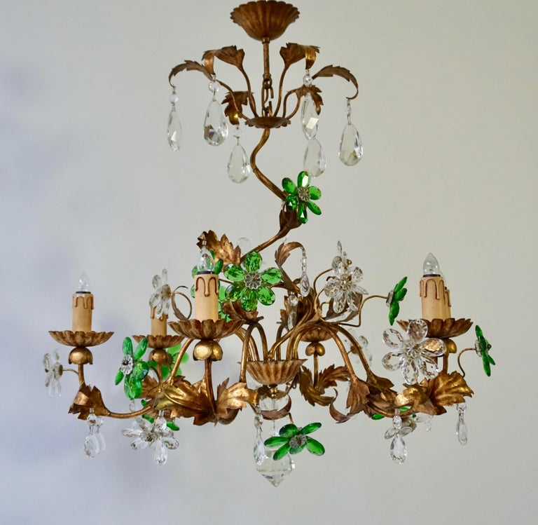 Floral Italian gilt iron chandelier, with glass flowers. The central stem, supports six E14 bulbs. The arms, fluidly interweave, with gilt leaves decorating throughout as well as green and transparent flowers. Measures: Diameter 75 cm. Height 80
