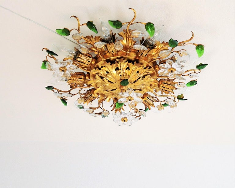Beautiful flush mount lighting made in Italy during the 1960s by Banci Florence. The ceiling light is made of big gilt metal leaves and has transparent flowers made in crystal glass and green leaves made of plastic. The light is adapted to be