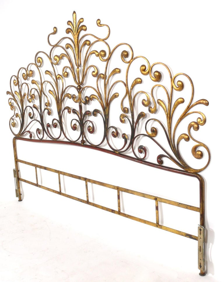 Glamorous gilt metal headboard, Italian, circa 1950s. It retains its original gilt finish with a wonderful patina with some overall wear to the gold leafed metal frame, exposing the Chinese red color underlayer or bole.