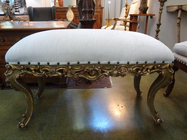Stunning Italian giltwood bench with exaggerated legs. This 1920s Italian bench was taken down to the frame and professionally upholstered in striated velvet with spaced brass nailhead detail. This versatile bench can be used in many design