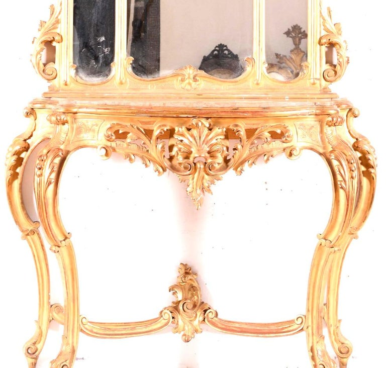 A fabulous Italian giltwood console table and mirror. Beautifully carved with very nice original gold leaf, the console with inset marble.  Highly decorative, with carved foliage throughout. (Marble can be changed to the customers