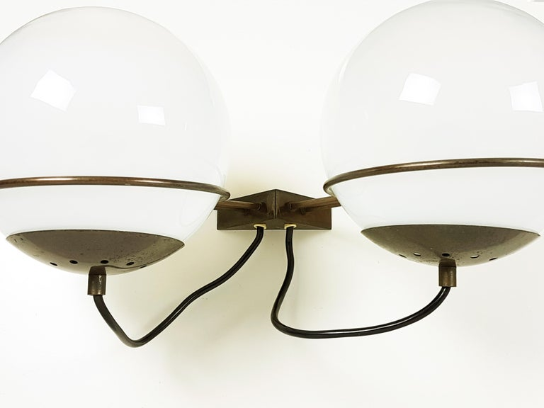 This pair of two-light sconces (mod. B519) was produced in Italy, circa 1960s by Candle. They are made from a bronzed brass structure with two hand blown spherical faded glass shades. Their design resemble similar items from Arteluce production.