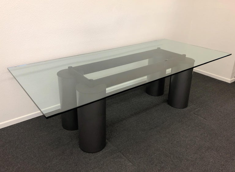 Italian Postmodern Memphis dining table designed by David Law, Lella & Massimo Vignelli for Acerbis International in the 1980s. The table is constructed of powder coated steel and glass. The cylinder legs are metallic gray powder coated steel. The