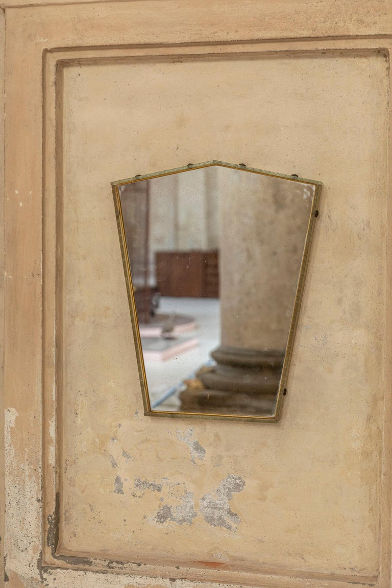 Wall mirror, produced in Italy, c. 1950s. Cut mirror glass is framed in a geometric shape glass frame. The frame presents carvings and the glass is in the shade of light brown.