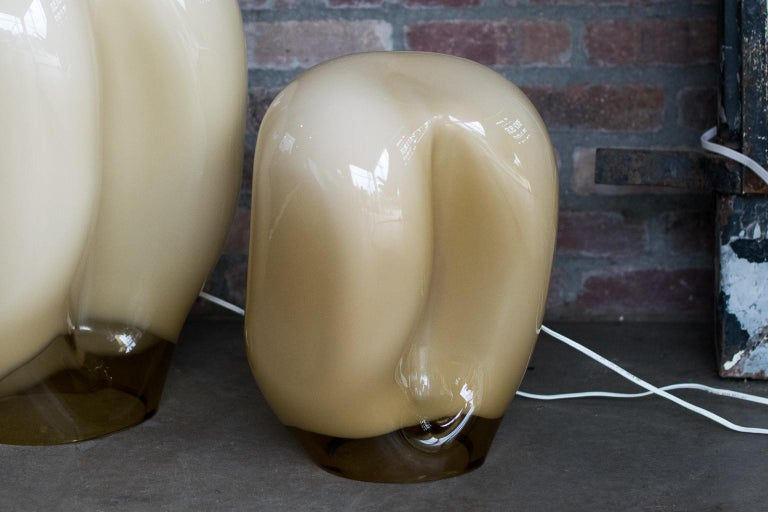 Sculptural Murano glass table lamp, designed by Gino Vistosi. Amorphic in form, color fades from opaque buff or beige to clear amber glass. Emits a warm white glow when lit. Late Mid-Century Modern to modern styling. One large and one small