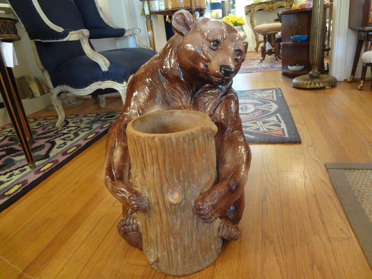 Unusual Italian glazed pottery or Majolica umbrella stand featuring a brown bear hugging a log or tree branch. This umbrella stand dates from the 1920s. This versatile Hollywood Regency piece has a Black Forest look and could also be used as a