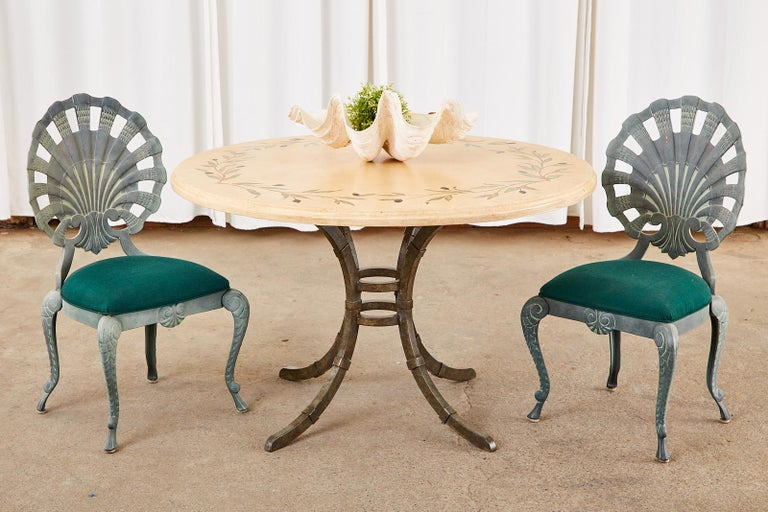 Country Italian style iron pedestal dining table or centre table featuring a thick glazed pottery ceramic top. The round top is decorated with a mosaic style olive branch design inlay around the border with a 1.5 inch thick ogee edge. Supported by a
