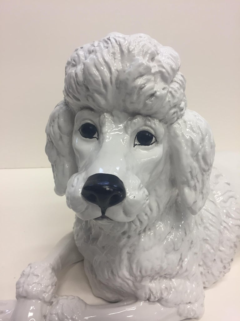 A poodle lovers dream glazed terracotta sculpture of an adorable pup with crossed front paws.