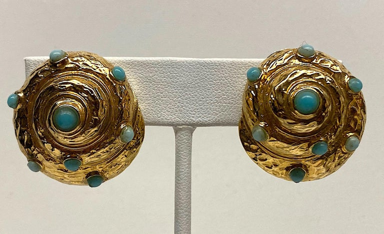 A nicely carved and detailed pair of spiral sea shell earrings circa 1980. The earrings are gold plate and set with two shades of faux turquoise cabochons. Each clip earring measures 1 inches wide, 1.13 inches tall and .5 of an inch high / deep not
