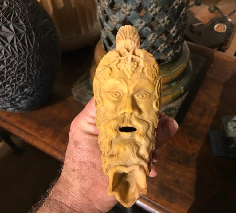 A wonderful oil lamp carved with the face of the Dionysus on a polished black marble base. Expertly carved depiction of the bearded god of wine with grapes in his hair. A souvenir of the 'Grand Tour', it is modeled after an ancient Roman original