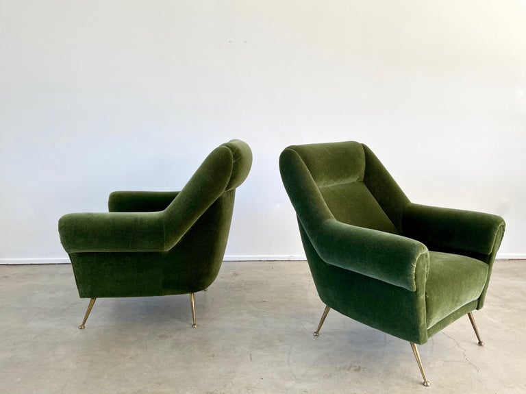 1950's Italian Lounge chairs reupholstered in olive green mohair with great curved arms and large in scale.   Solid brass legs with great patina.