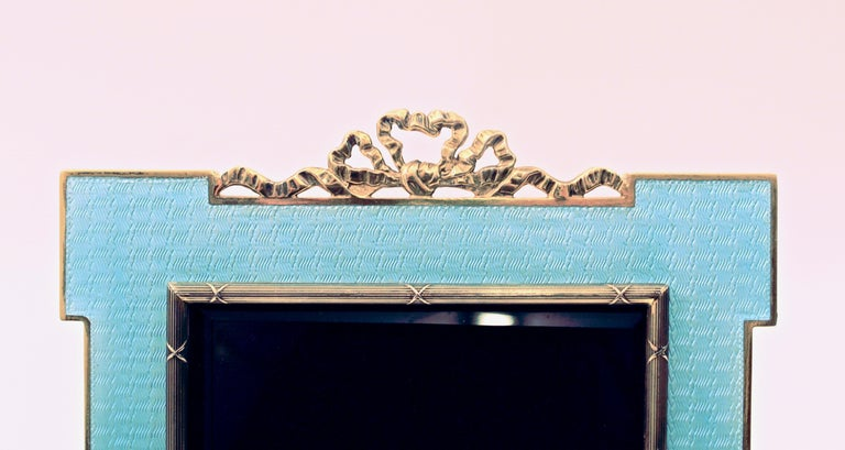 Light blue guilloche fire enamel photo frame, circa 1970. The rectangular frame, with square corners and a central ribbon crest, the central aperture with a ribbon and reed border. The 925 stamped gold plated silver body, bearing makers mark for