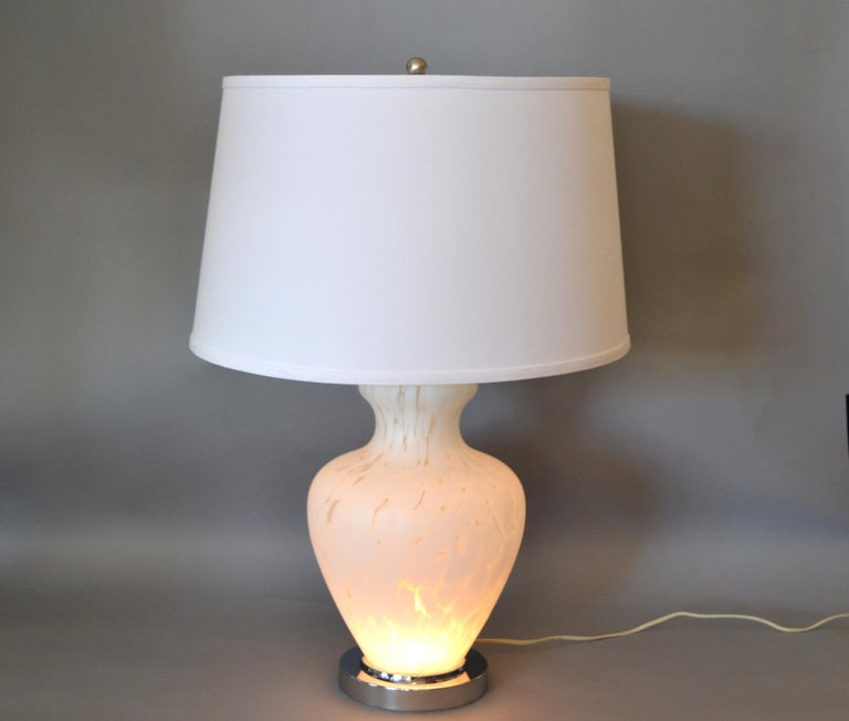 We are presenting an Italian hand blown Murano glass table lamp with chrome base and chrome neck. It is wired for the U.S. and uses 2 max. 60 watts light bulbs. The bottom lights up and the top in two different turns of the switch. Comes with harp