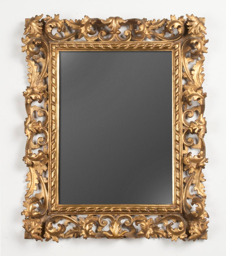 A late 19th century baroque revival wooden mirror from Italy. Refined hand carved from poplar wood. The frame is completely gold leaf gilt. The frame is deeply carved with scrolls and acanthus fronds. Mirror glass. For it's modest size, it is