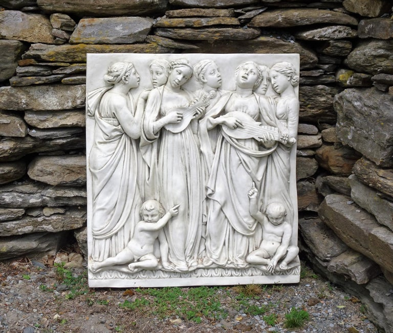 This is a large, high-relief wall hanging in midcentury Italian fiberglass. It is in the neoclassical style and depicts seven of the mortal daughters of Jupiter. They are singing, while two of them play stringed instruments, and they are standing