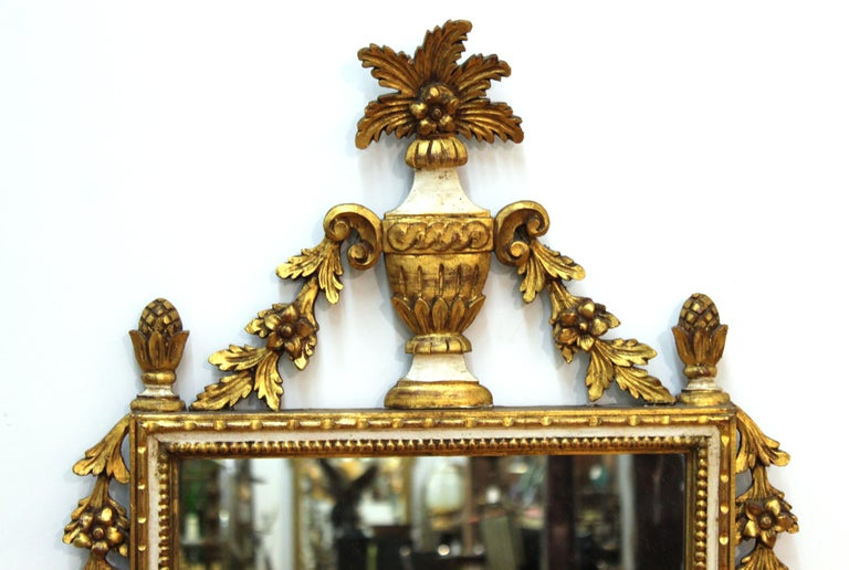 Italian Hollywood Regency partially gilt and painted carved wood wall mirror in neoclassical Revival style.