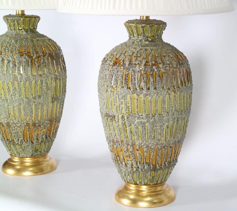 Italian Hollywood Regency ceramic lamps with a textured drip glaze in green and gold tones. Each is mounted to a gilded wooden base. These lamps date from the 1950s and are in excellent vintage condition having wear consistent with age and use.