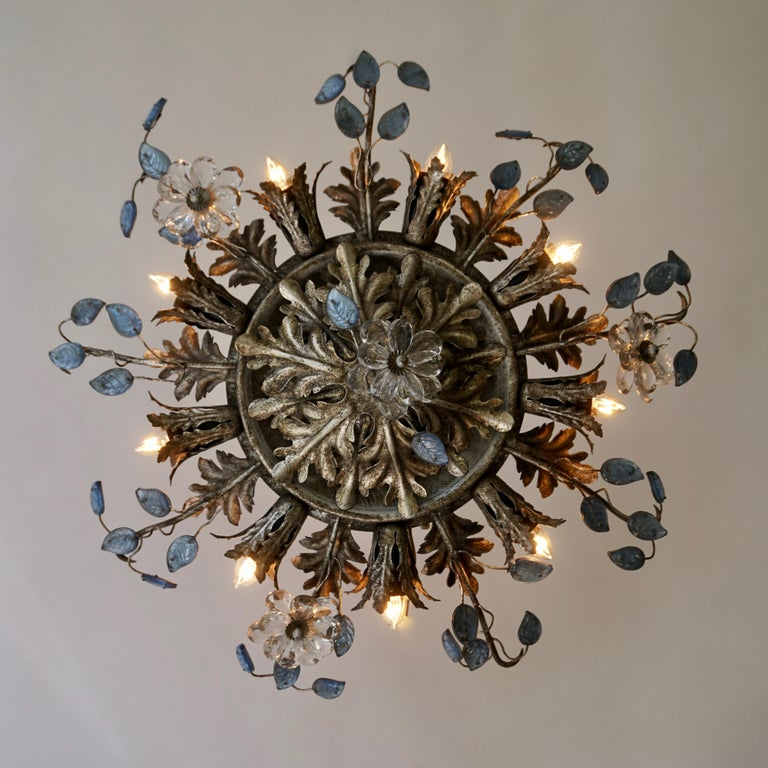 Beautiful flush mount fixture which can be used also as wall sconce - this Italian light with metals leaves, small blue glass leaves and transparent flowers is gorgeous! The light fixture has 9-light bulb holders spread around as a sunburst. With