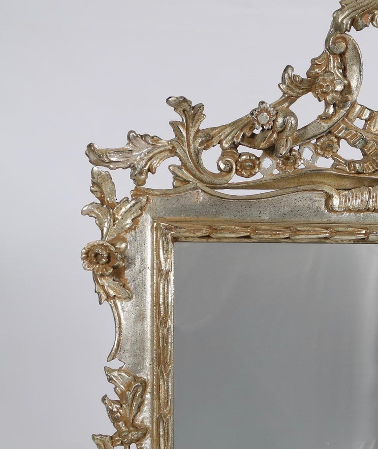 Italian Hollywood Regency mirror made of carved wood with silver leaf. The mirror features intricate carved scroll work with flowers and fruits. Wear appropriate to age and use. The mirror remains in excellent vintage condition.