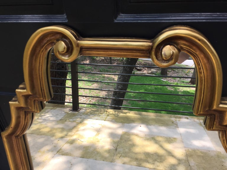 1960s La Barge wooden mirror with a gilt finish. Geometric sides lead to a scrolled top, giving this mirror transitional appeal. French style curved accents at top compliment its contemporary lines. Unmarked.