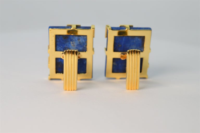 Vivid blue lapis lazuli stone tiles accented with eighteen 18k yellow gold create this modernist pair of unisex cufflinks. With an artful circular pattern, gold partially overlays the blue stone letting the blue color and natural  beauty of the