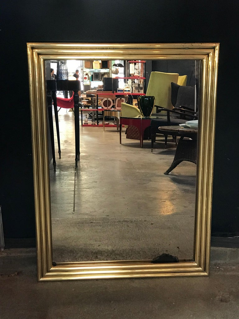 An Italian mirror with brass surround from the midcentury. This simple and elegant vintage Italian mirror features a rectangular shape with brass surround, which has a lovely patina throughout. This is a good sized mirror. The clean lines allowing