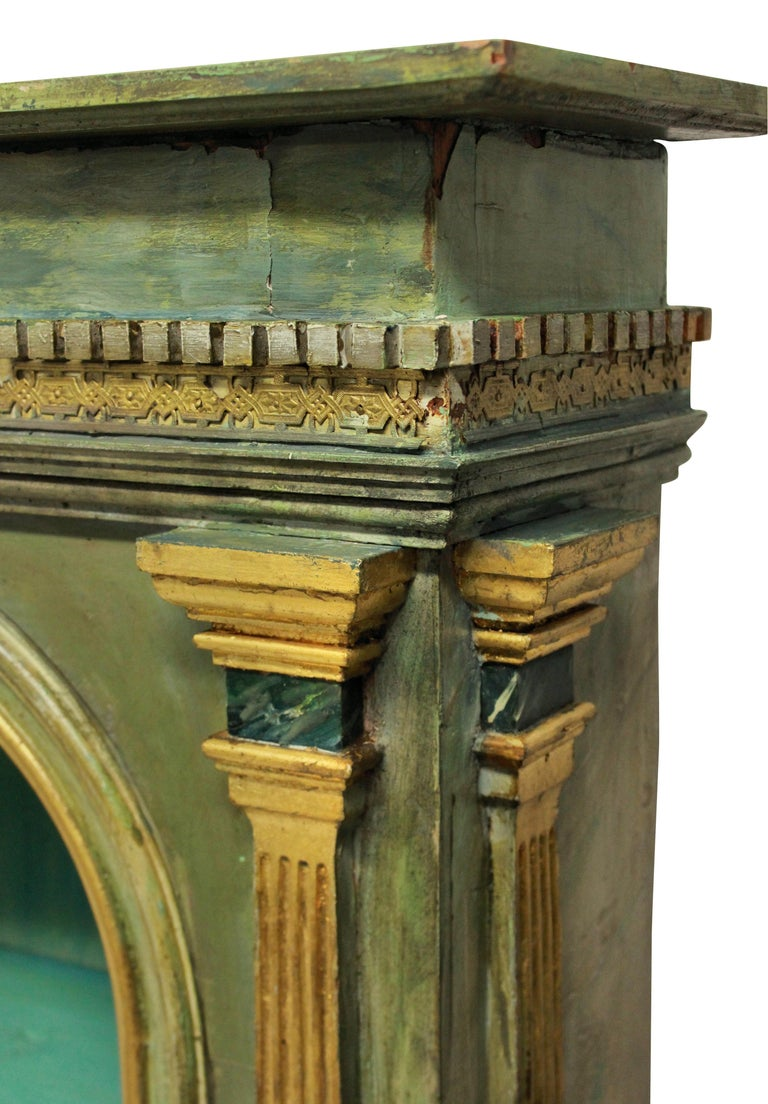 An Italian late 18th century curiosity cabinet in a classical manner in faux marble with water gilding. The pediment with a filigree gilt bronze frieze. Later restored and the door formerly glazed.