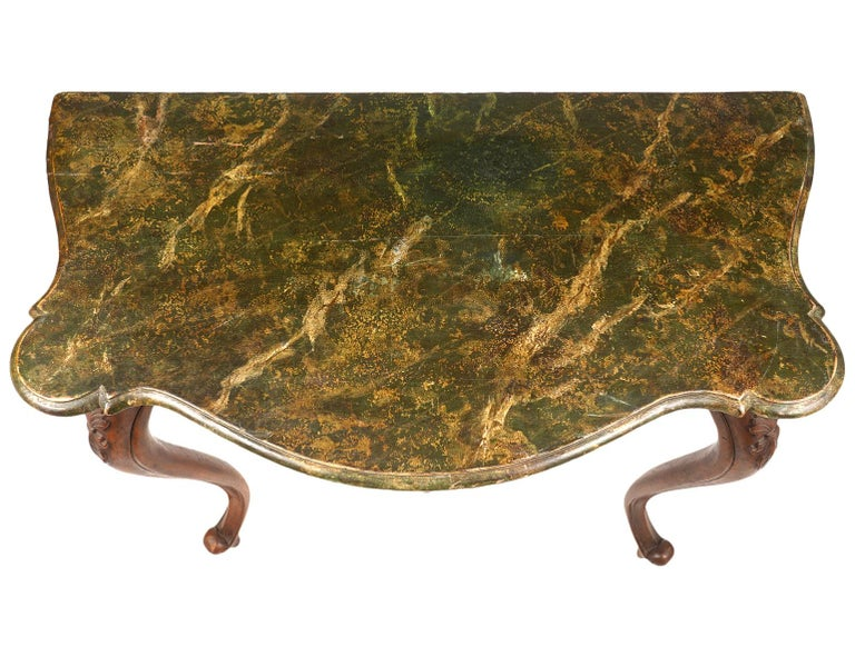 Resting on four boldly carved cabriole legs, the rear legs turned sideways, this Italian walnut console table, dating to the late 19th century, features a marbleized painted top above shaped aprons centering carved shells and scrolls on three sides.