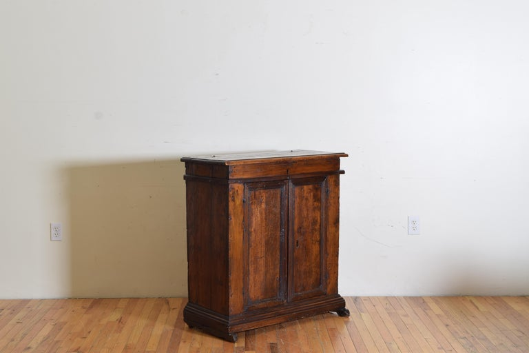Having a hinged rectangular top with a molded edge opening to reveal a locking upper storage well above a conforming case with paneled doors and an interior with shelving, resting on a graduated plinth form base raised on original carved feet.