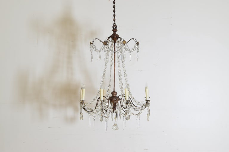 This chandelier is based upon a central wrought iron rod with turned a turned giltwood top and bottom, the top portion with gilt metal stars, both issuing thin iron arms with metal bobeches, the arms joined by glass prism chains, now wired
