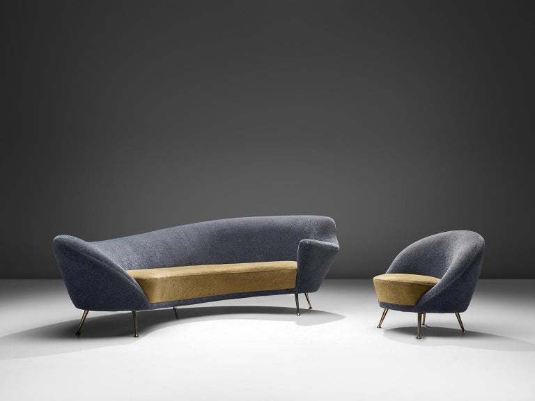 Curved sofa and easy chair, yellow and blue fabric, brass, Italy, 1950s.  This elegant set features a dynamic sofa with an a-symmetrical back and a club chair. The back of the sofa is higher on the right side and slowly slopes towards much lower