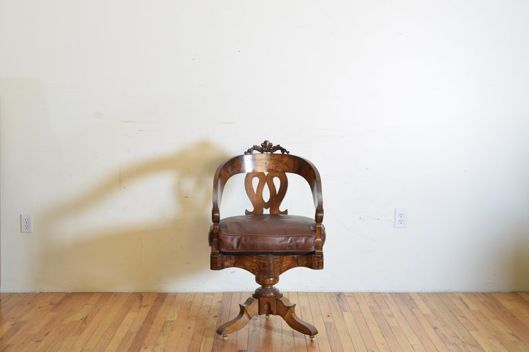 Having a barrel back and a carved finial and shaped splat this swiveling desk chair is raised on a tripartite base with shaped feet, the brass casters and leather cushion are later additions.
