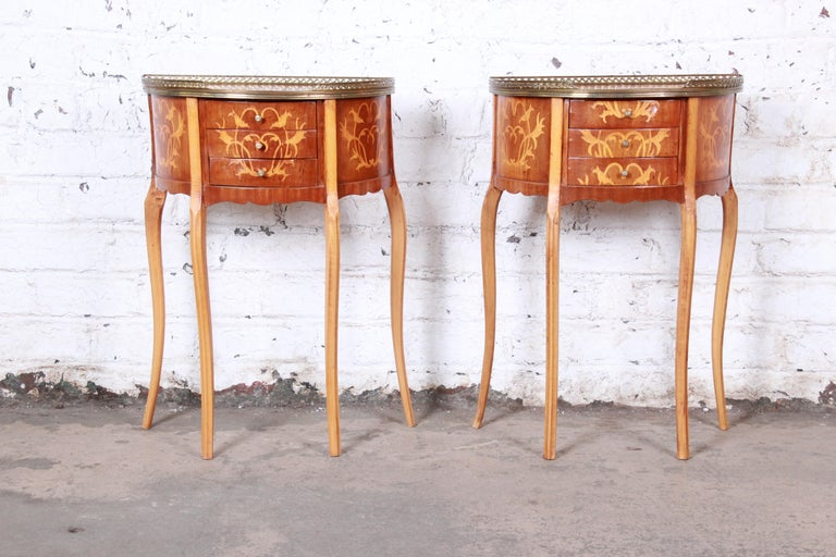 A gorgeous pair of petite Italian Louis XV style inlaid marquetry mahogany three-drawer demilune nightstands or side tables  Italy, circa 1930s  Mahogany, satinwood inlay and brass gallery and hardware  Measures: 19.38