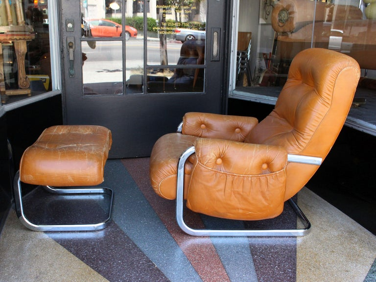 1960s Italian leather lounge chair with the ottoman. The side of the chair is the pocket for the newspaper. Chrome base and leather exceptionally comfortable.