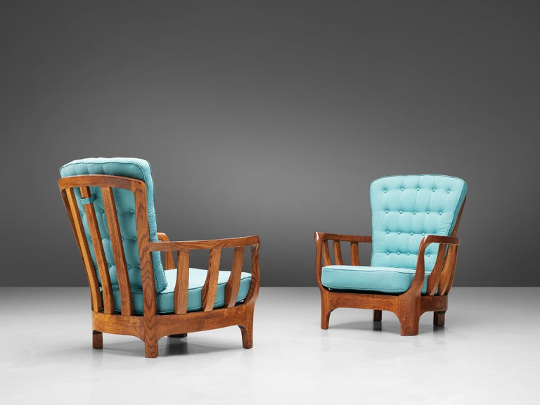 Pair of lounge chairs, oak and fabric, Italy, 1960s.  This sculptural set of Italian armchairs is very well executed and made out of solid, carved oak. The robust chairs feature wonderfully curved armrests with slats. The high back features an