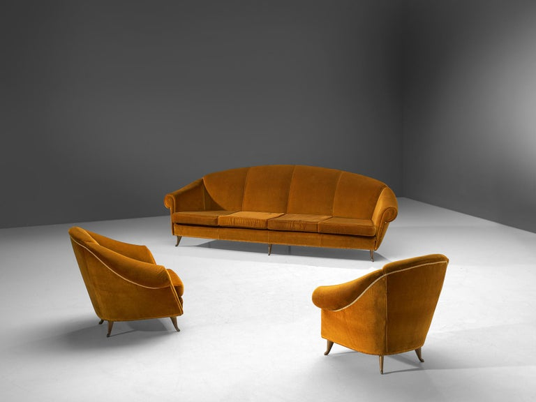 Living room set, velvet and brass, Italy, 1940s  This voluptuous, elegant set, consisting of a four-seat sofa and two lounge chairs, features high, to ascended backs that flow over to the thick, curled armrests. These features give these chairs