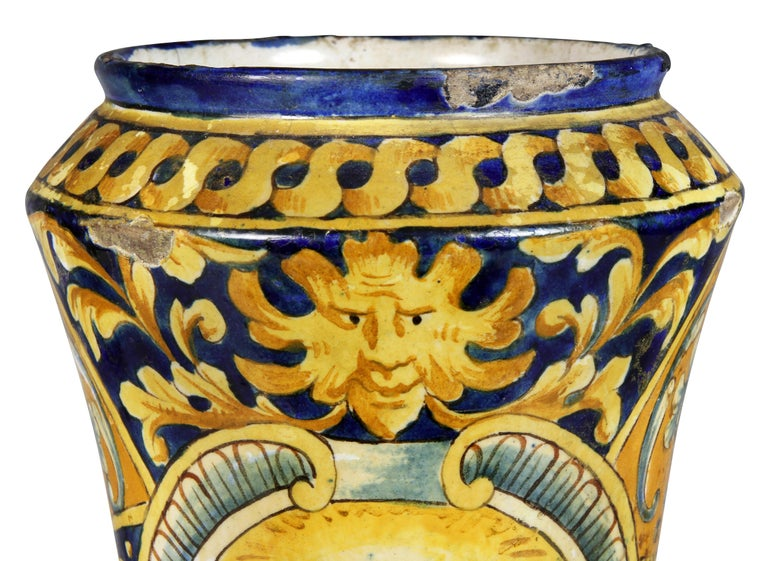 Cylindrical with concave sides and circular base. Decorated with a figure of a Roman within a cartouche, decorated overall with geometric design with scrolling leaves.