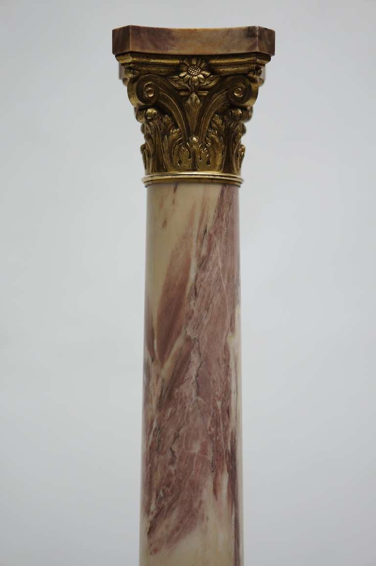A marble column (pedestal) with a bronze Corinthian capital.
