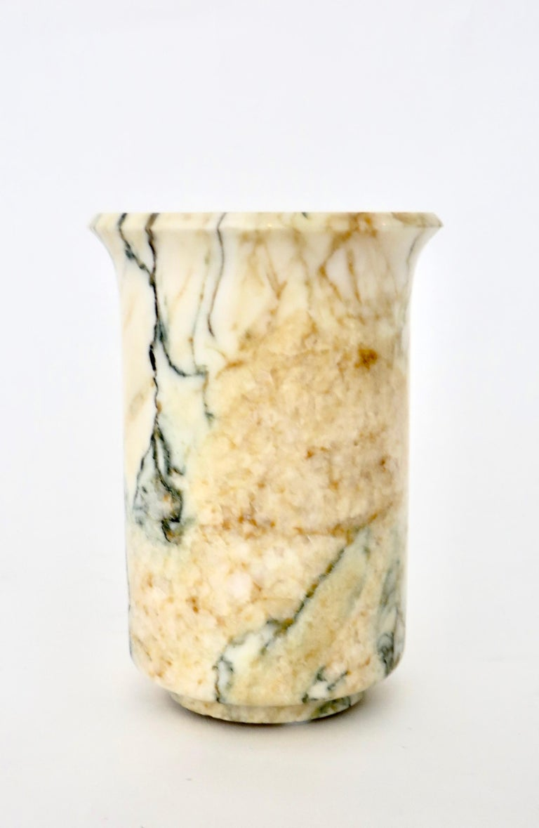 Italian polished marble vase in creams and gold with blue black green veining.