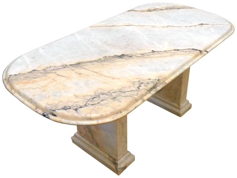 A massive and impressive Italian marble dining table. An aesthetic fusion of classical and modern forms, beautifully executed in rich, figured stone. A dual-pedestal leg structure supports a single-slab, radiused rectangular and double-beveled top.
