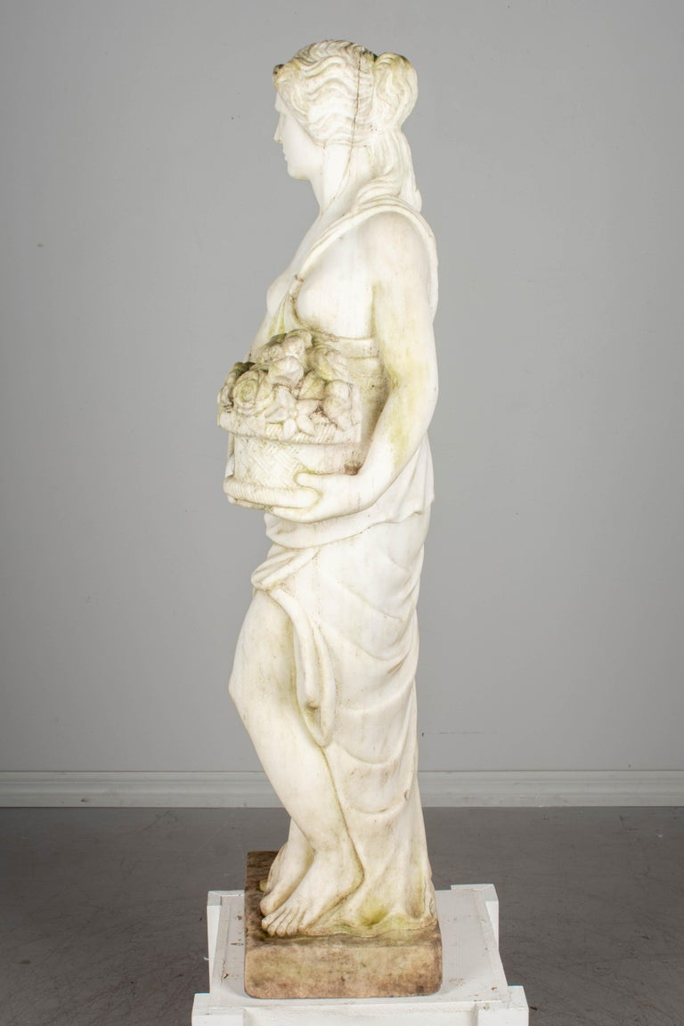 A finely carved Italian white marble Allegory of Spring garden statue depicting a lovely young maiden standing in a Classical Greek pose and holding a basket of flowers. Carved in several parts and retaining a weathered patina. Please refer to