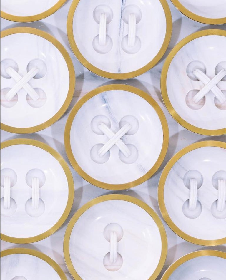 In this beautiful piece you can appreciate White Lasa marble for a motif that plays innocently with the theme of buttons. Created in Italy and designed by Ferruccio Laviani. Large concave marble buttons 40cm in diameter with two or four holes are