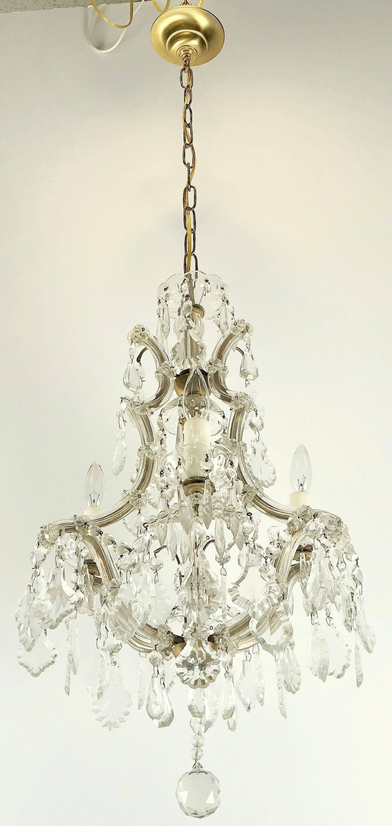 A lovely Maria Theresa four-light chandelier (or hanging fixture) of crystal, glass and gilt metal featuring serpentine arms, each candle light with dangling pendants and decorative bobeches.
