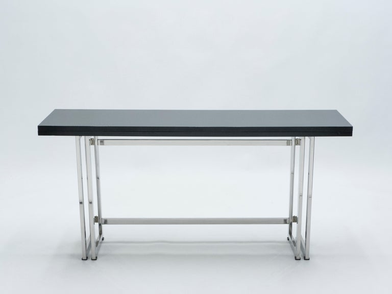 With a beautiful black lacquered top, sharply geometric chrome metal legs and a foldable body to fit your particular spatial needs, this mid-century italian console table by Artelano carries a stellar futuristic mid-century aesthetic into the