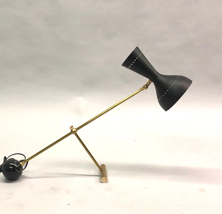Elegant Italian Mid-Century Modern style desk or table lamp in the style of Angelo Lelli for Arredoluce composed of a round ball black marble base anchoring a solid brass articulating stem and a black enameled double shade with 1 socket in each