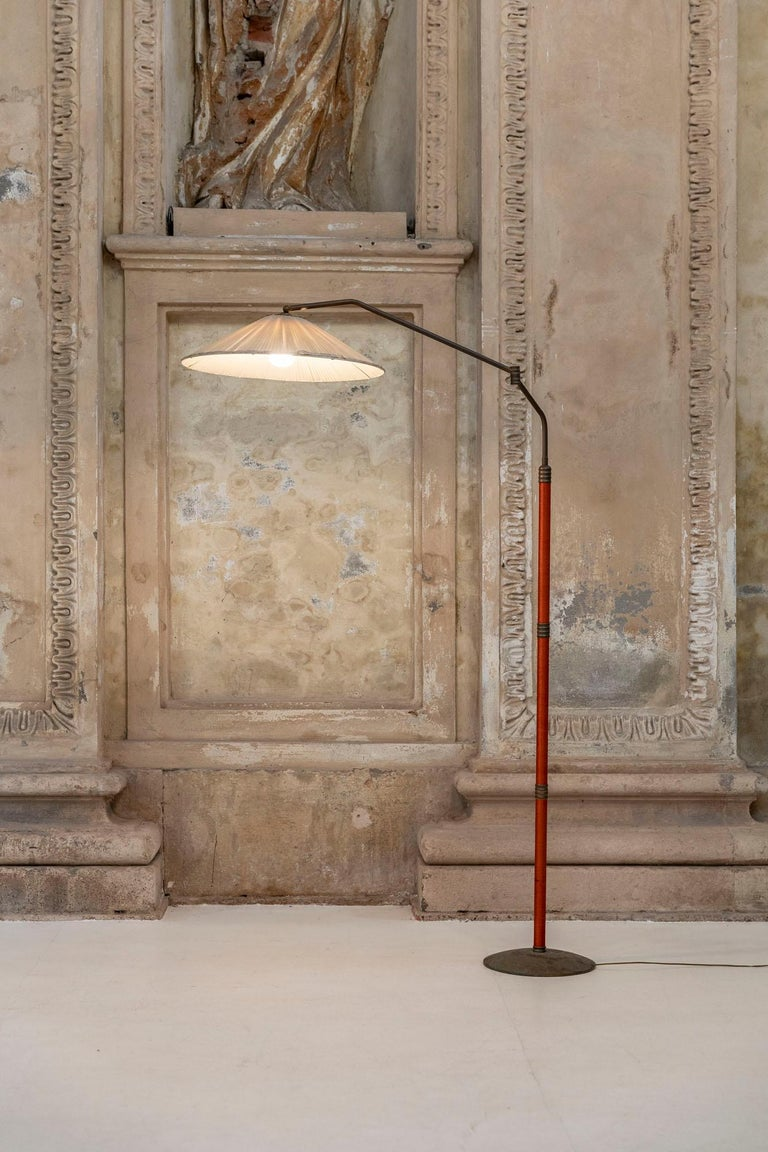 Mid-century brass floor lamp  The lamp consists of a brass base that support a brass rod that is adjustable in height and in the length.  The original lampshade is made in pleated fabric, beautiful orange silk wires along the structure.
