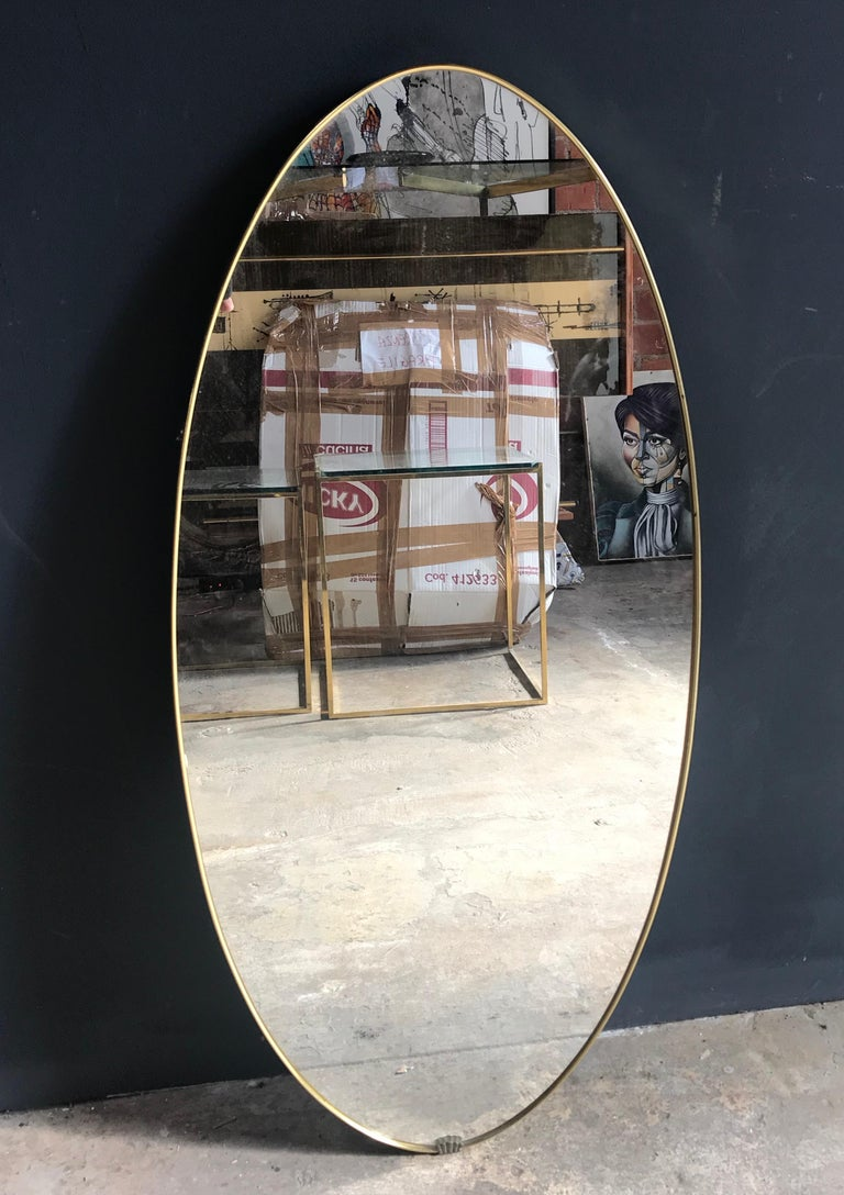 Midcentury brass oval mirror with little shell on the frame, Italy, 1950s.